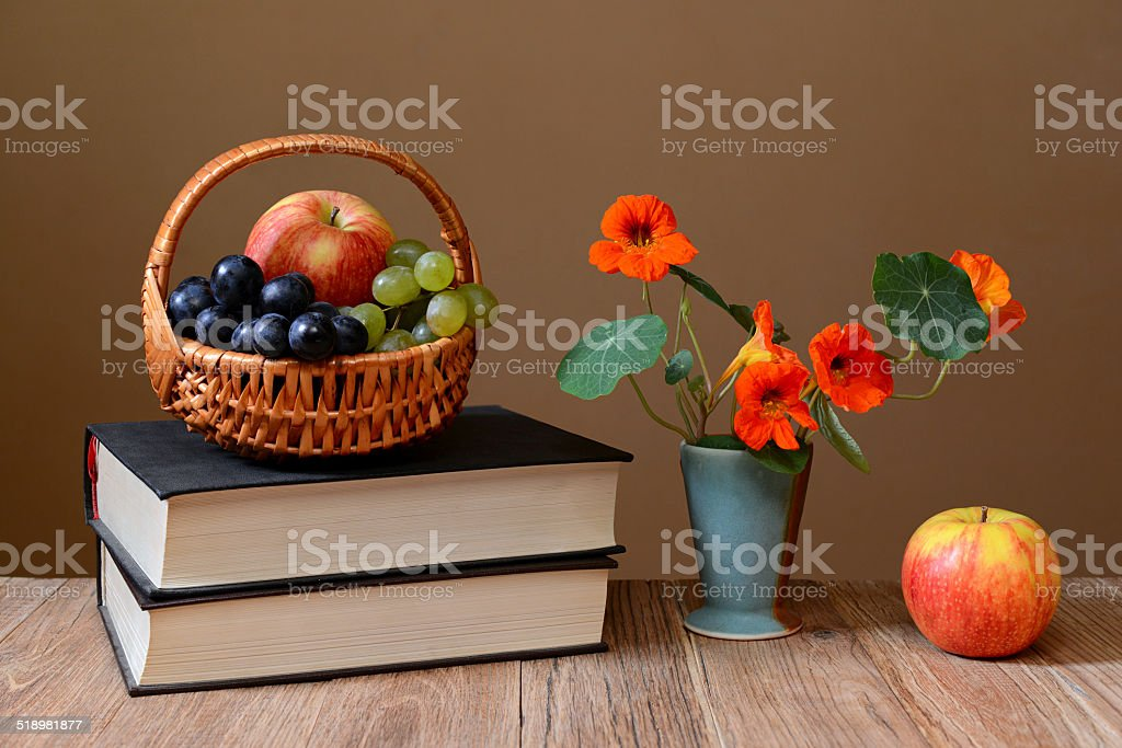 Fresh fruit in the of basket wicker, books and flowers stock photo