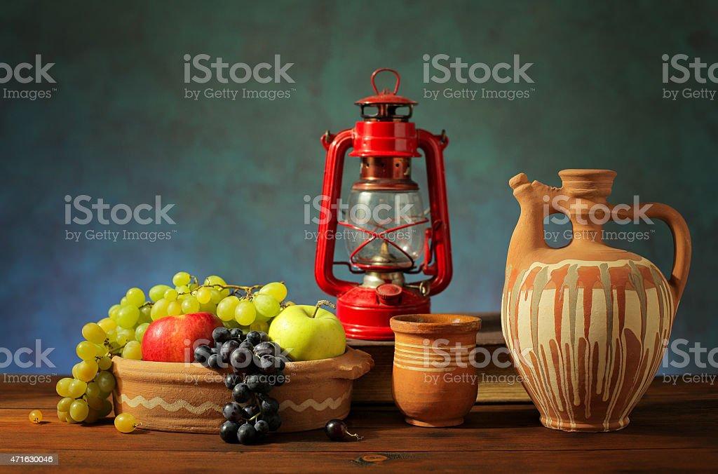 Fresh fruit, lantern and ceramic dishes stock photo