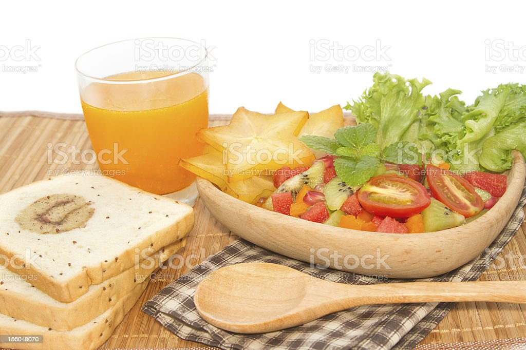 Fresh fruit salad with orange juice and slice bread, royalty-free stock photo