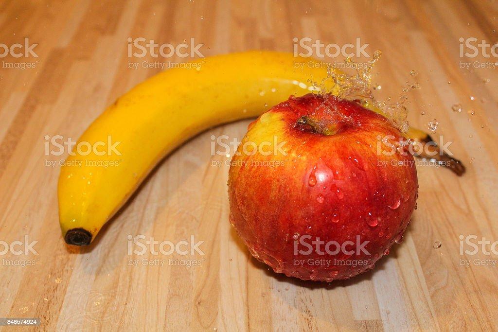 Fresh fruits apple and banana with water splash on wood background stock photo