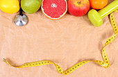 Fresh fruits, centimeter, stethoscope and dumbbells for fitness, healthy lifestyles