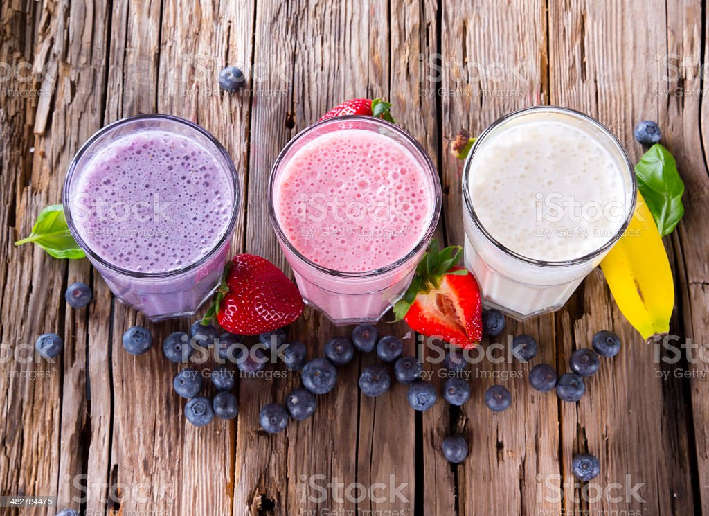 Fresh fruits milk shake on wood stock photo