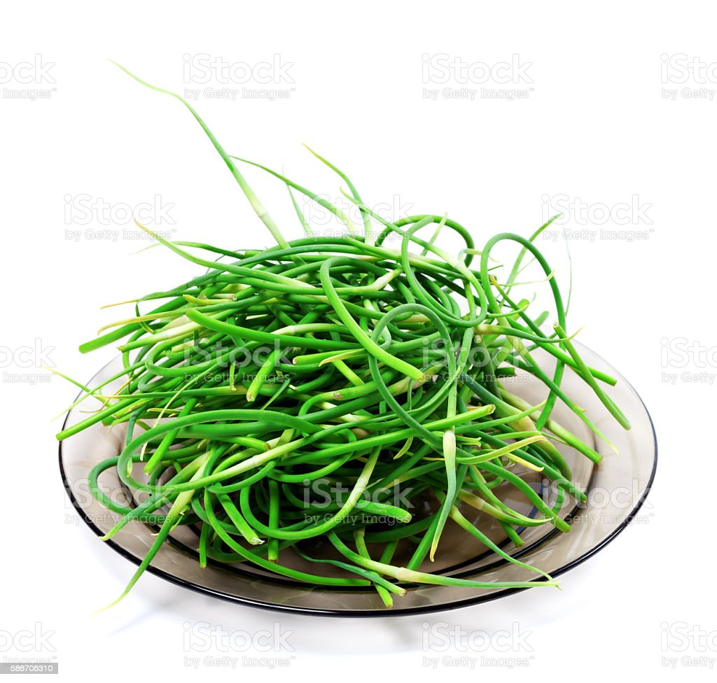 Fresh garlic scapes on glass plate stock photo