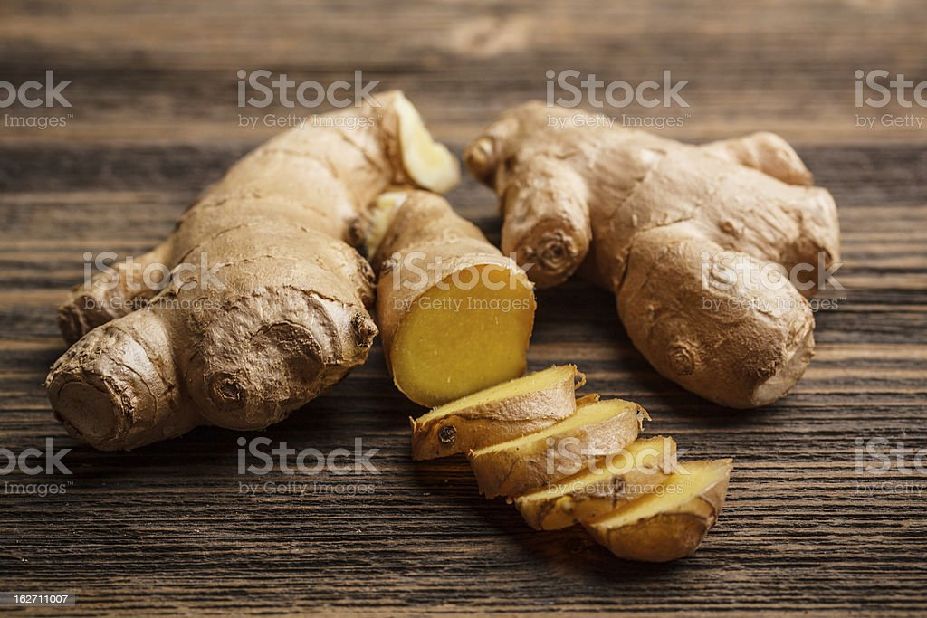 Fresh ginger whole and chopped on rustic wood surface stock photo