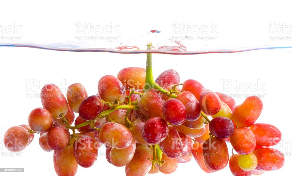 fresh grape dropped into water with splash isolated on white royalty-free stock photo