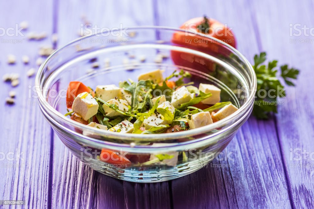 Fresh Greek salad in a bowl near tomate , top view on wooden table stock photo