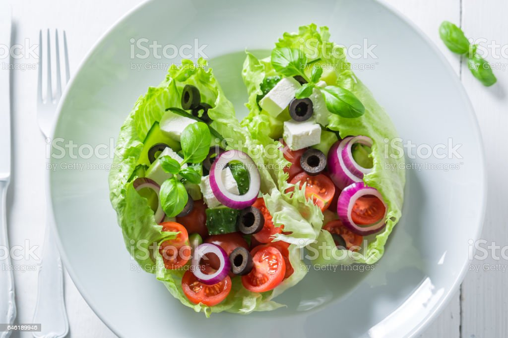 Fresh Greek salad with feta cheese, black olives and lettuce stock photo