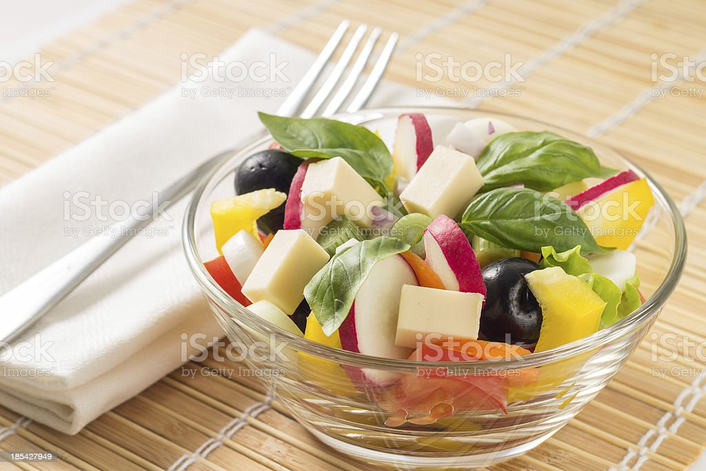 Fresh greek salad with fork on bamboo background royalty-free stock photo