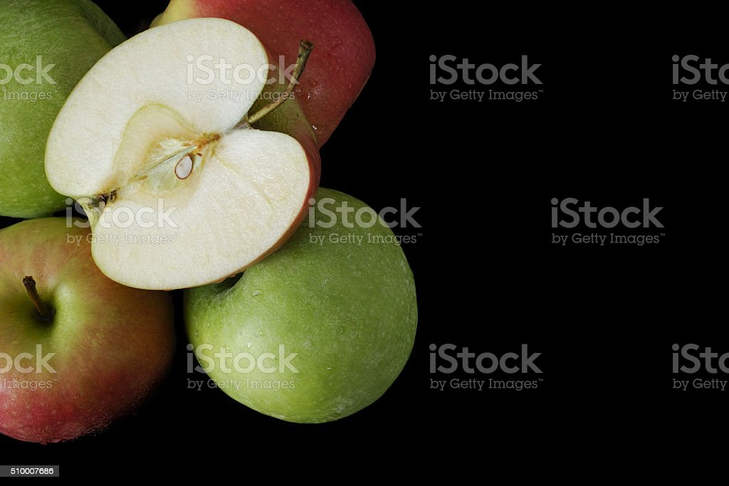 Fresh green and pink apples on black background, closeup stock photo