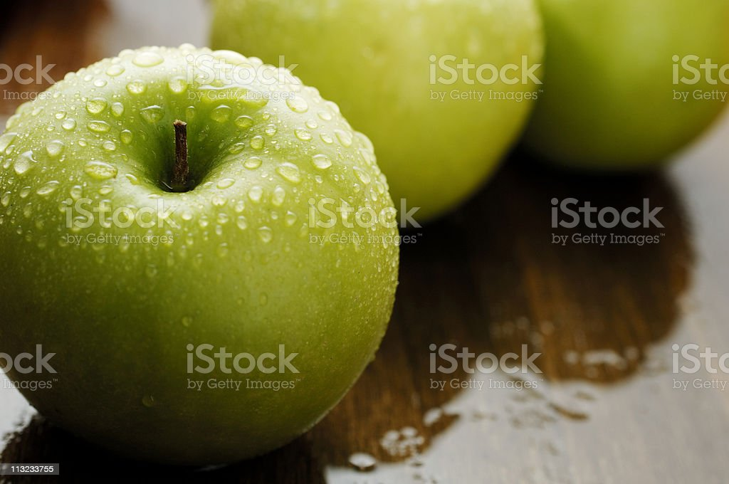 fresh green apple covered in water against dark wet oak royalty-free stock photo