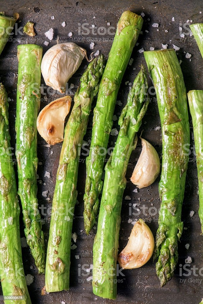 Fresh green asparagus with garlic cooking in a metal skilletFres stock photo