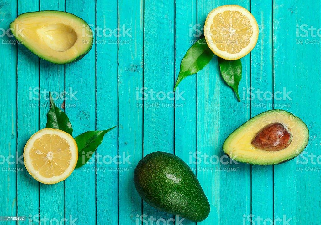 Fresh green avocado and yellow lemons stock photo