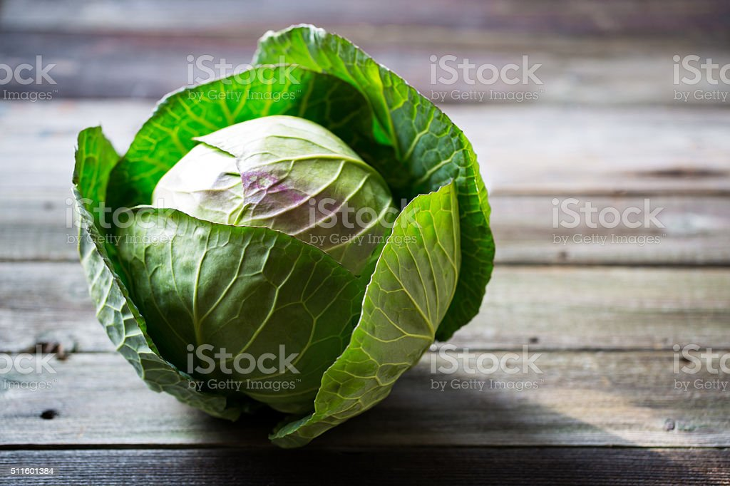 Fresh green garden cabbage on rustic wooden background stock photo