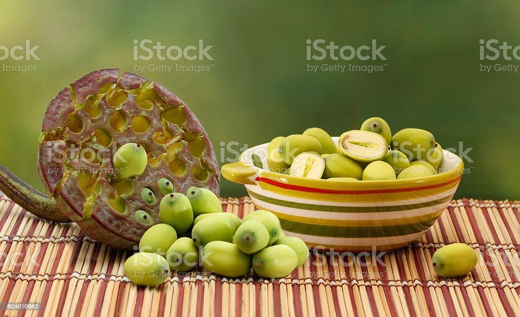 Fresh green lotus nuts in ceramic bowl and lotus seedbox stock photo