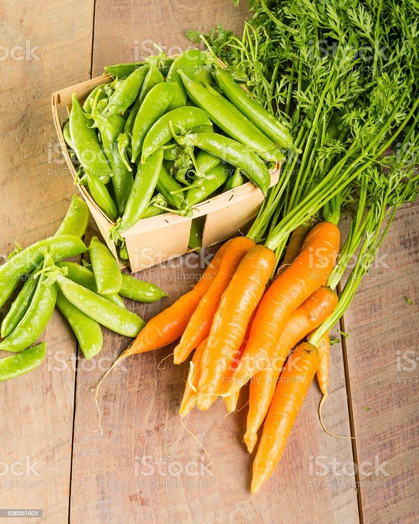 Fresh green peas and carrots stock photo