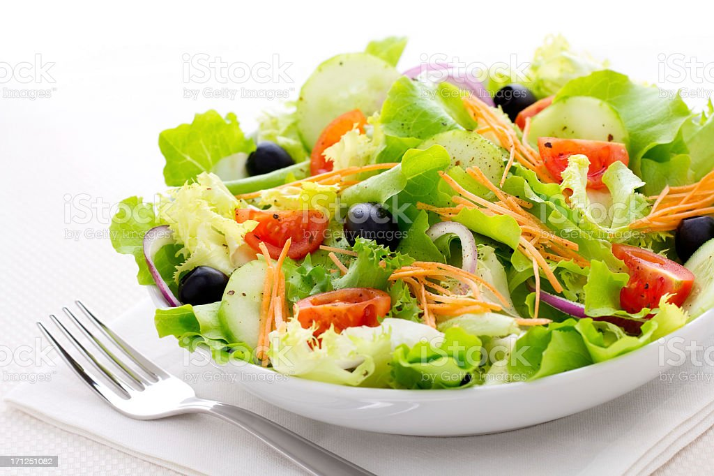 Fresh green salad with a fork in a white bowl stock photo
