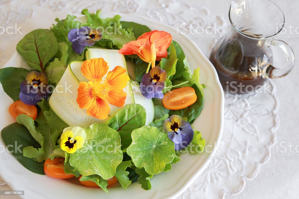 Fresh green salad with edible flowers stock photo