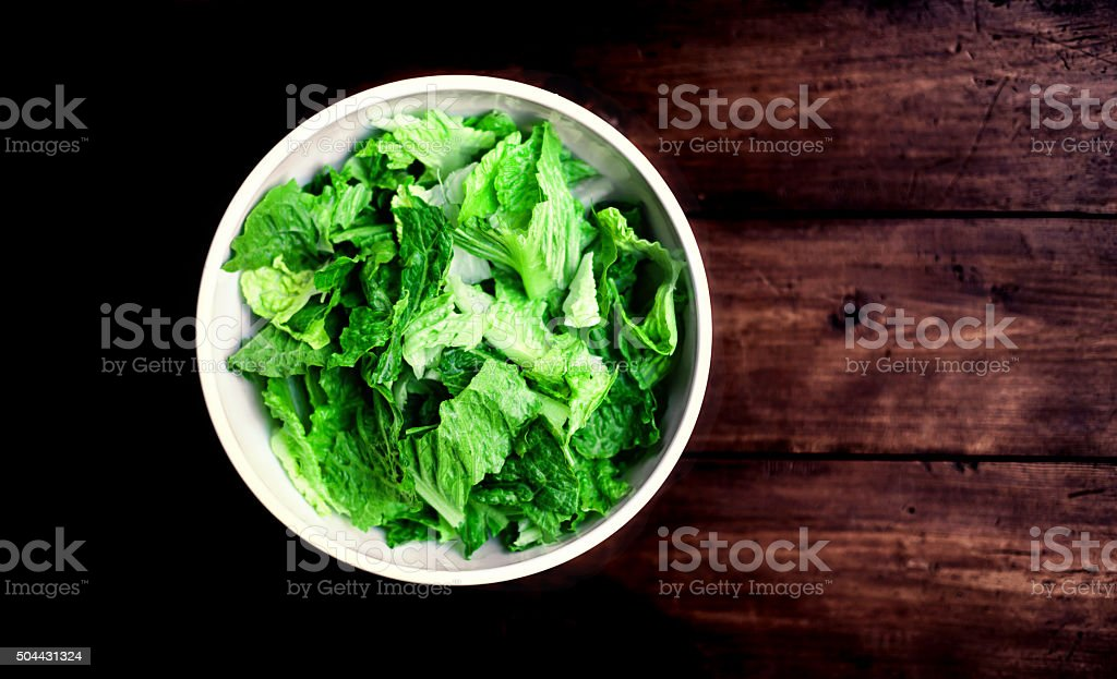 Fresh green salad with spinach, arugula and lettuce over wooden stock photo