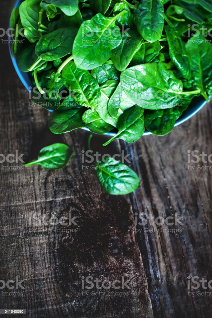 Fresh green spinach in blue bowl on the dark wood background with copy space stock photo