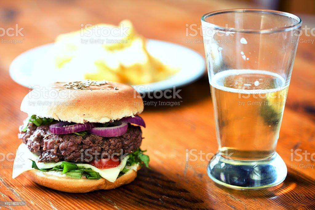 Fresh hamburger with beer and fried potatoes royalty-free stock photo