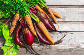 fresh harvested carrots and beetroots on rustic wooden backgroun