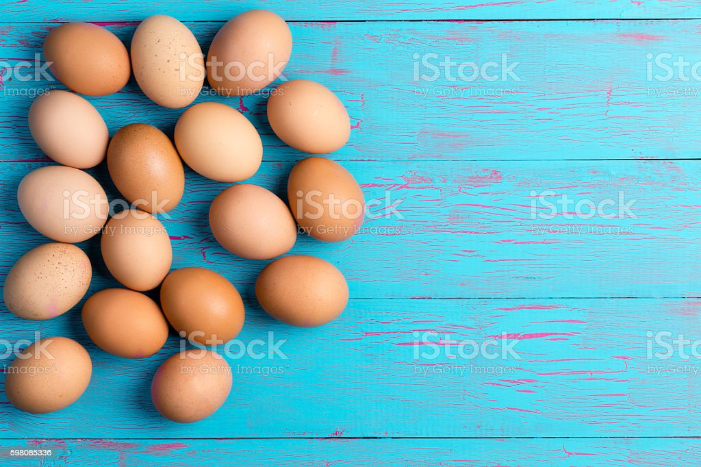 Fresh healthy brown eggs on a colorful blue table stock photo