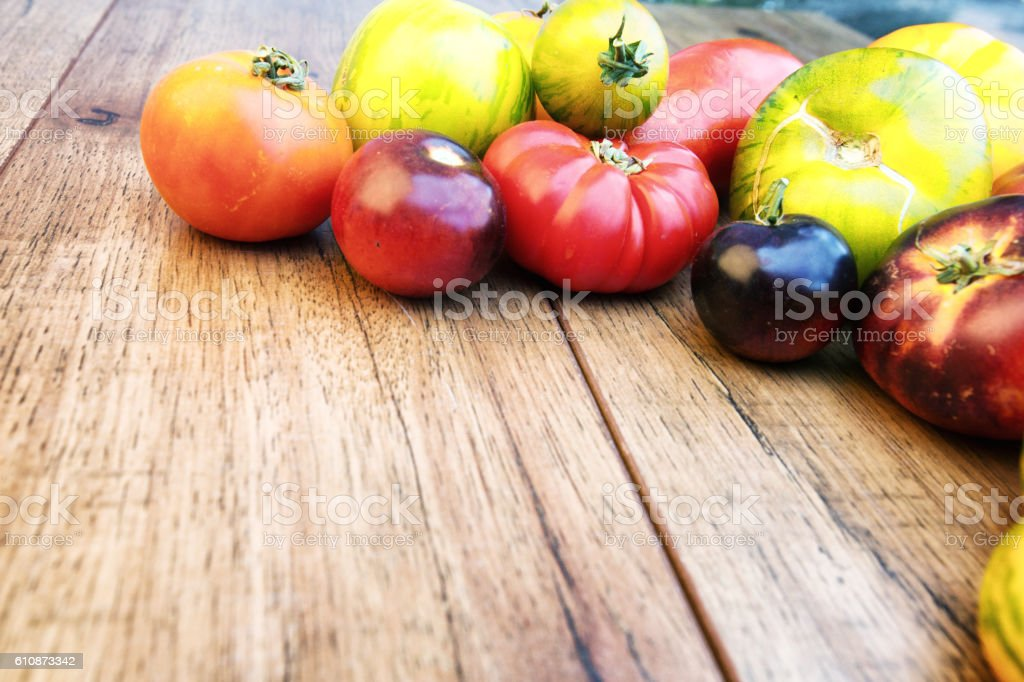 Fresh Heirloom Tomatoes on a Rustic Cutting Board Background stock photo