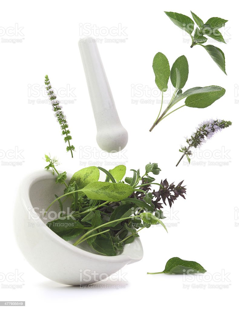 Fresh herbs falling into a porcelain mortar royalty-free stock photo