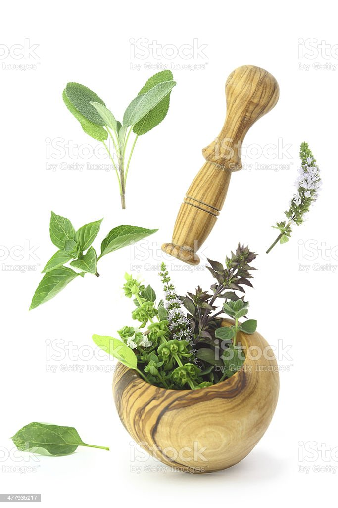 Fresh herbs falling into a wooden mortar royalty-free stock photo