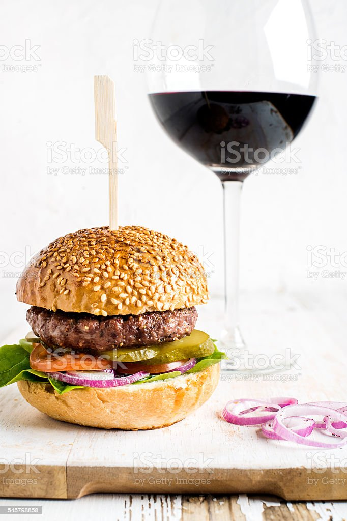 Fresh homemade burger on white wooden serving board with onion stock photo