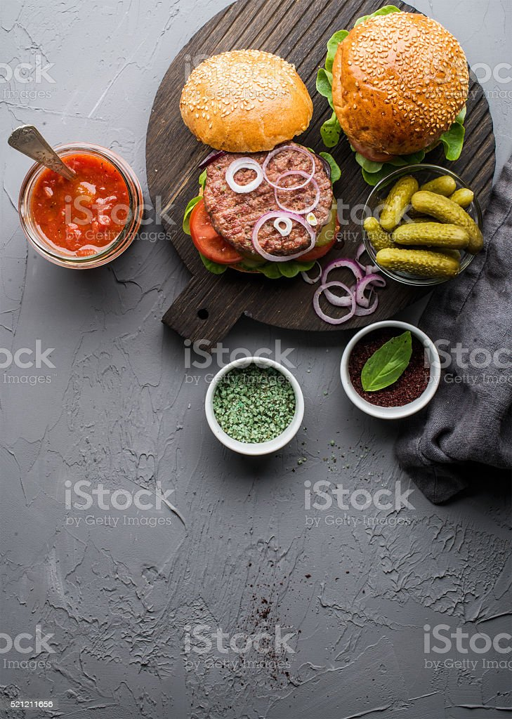 Fresh homemade burgers on dark serving board with spicy tomato stock photo