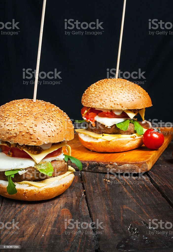 Fresh homemade burgers on wooden board stock photo