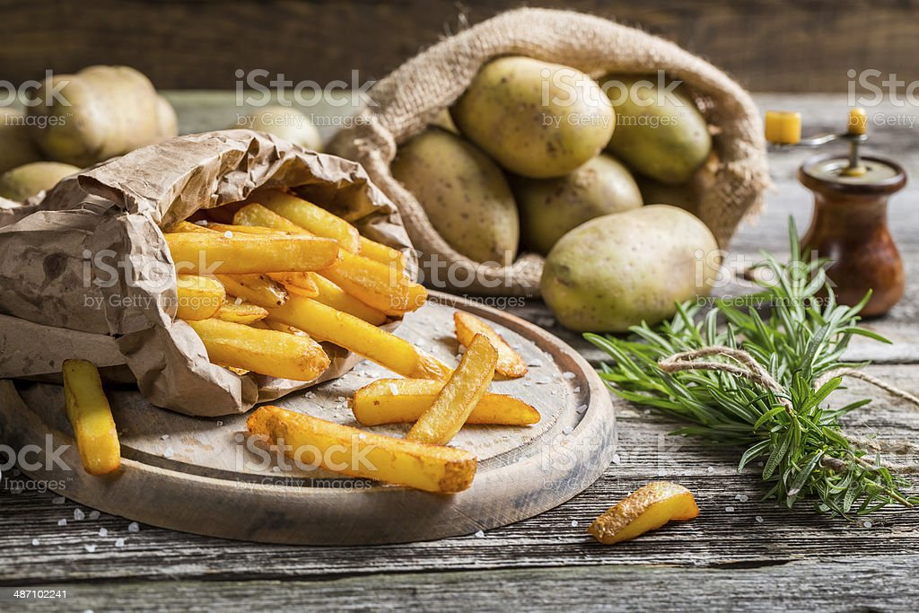 Fresh homemade fries with salt served in paper stock photo