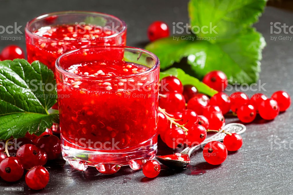 Fresh homemade jam rubbed red currants in a glass stock photo