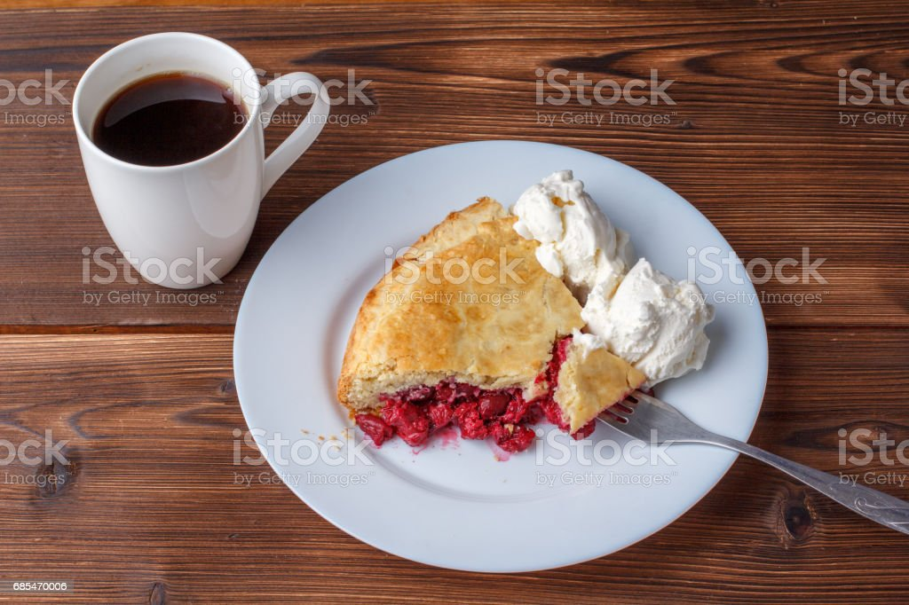 Fresh homemade pie with cherry pulp and ice cream on a plate. A slice of a cherry pie with a ruddy crust on a wooden table. Cherry pie and mug of delicious hot black coffee. stock photo