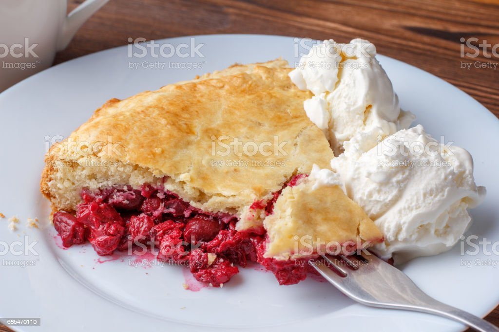Fresh homemade pie with cherry pulp and ice cream on a plate. A slice of a cherry pie with a ruddy crust on a wooden table. stock photo