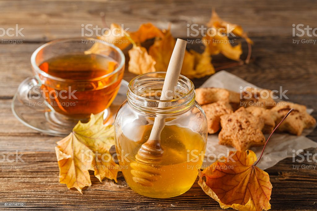 fresh honey and cup of tea  on a wooden background stock photo