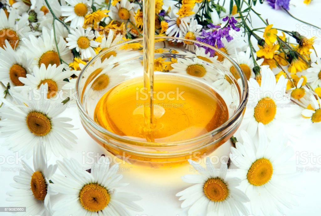 fresh honey flows into a bowl and flowers stock photo