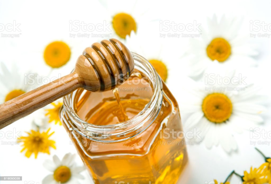 fresh honey in a bank and honey stick and flowers stock photo
