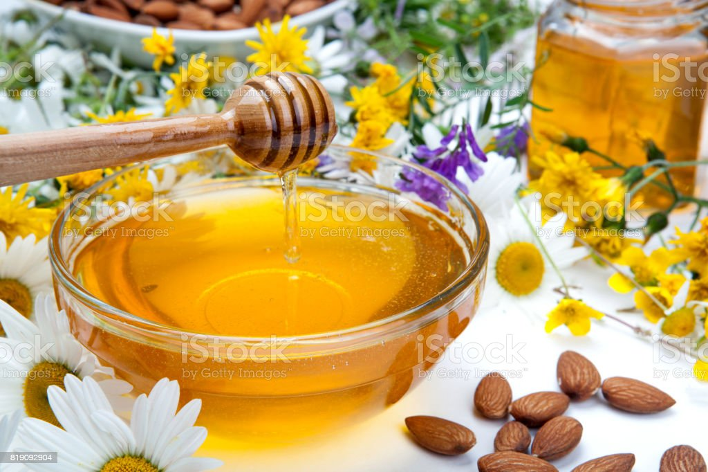 fresh honey in a bowl and honey stick and flowers stock photo