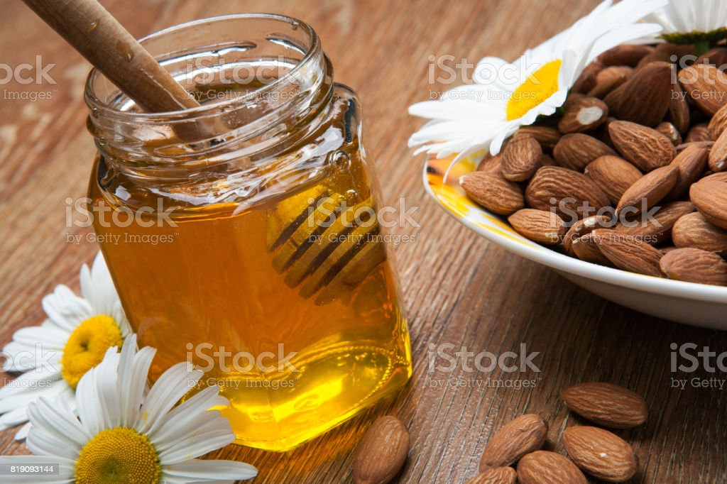 fresh honey in the bank and honey stick and flowers and almond stock photo