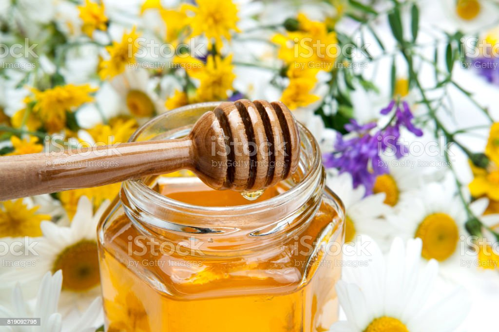 fresh honey in the bank and honey stick and flowers stock photo