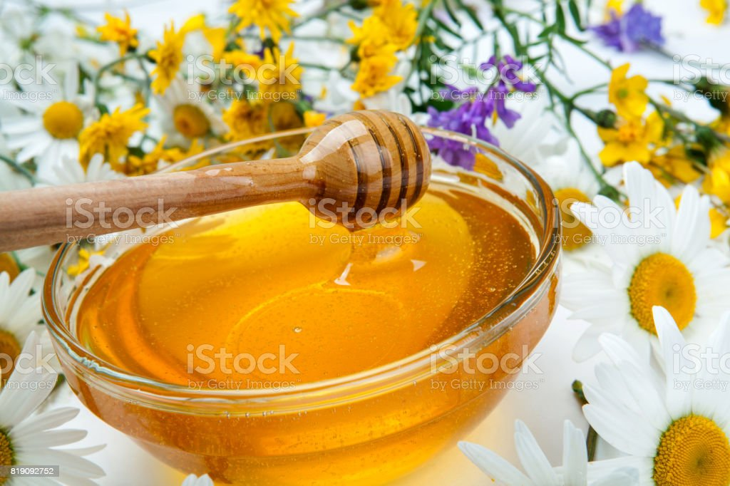 fresh honey in the bowl and honey stick and flowers stock photo
