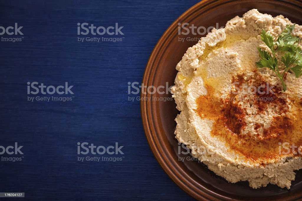 Fresh hummus with cilantro in brown bowl on blue table stock photo