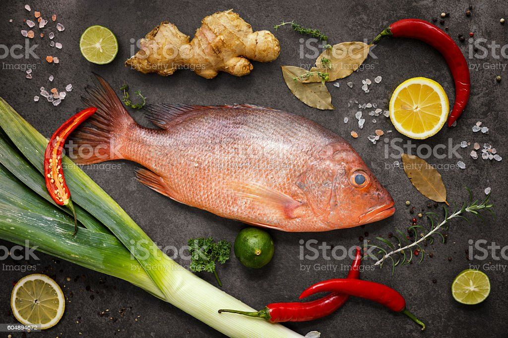 Fresh ingredients to cook fish, red snapper, leak, lime, lemon stock photo