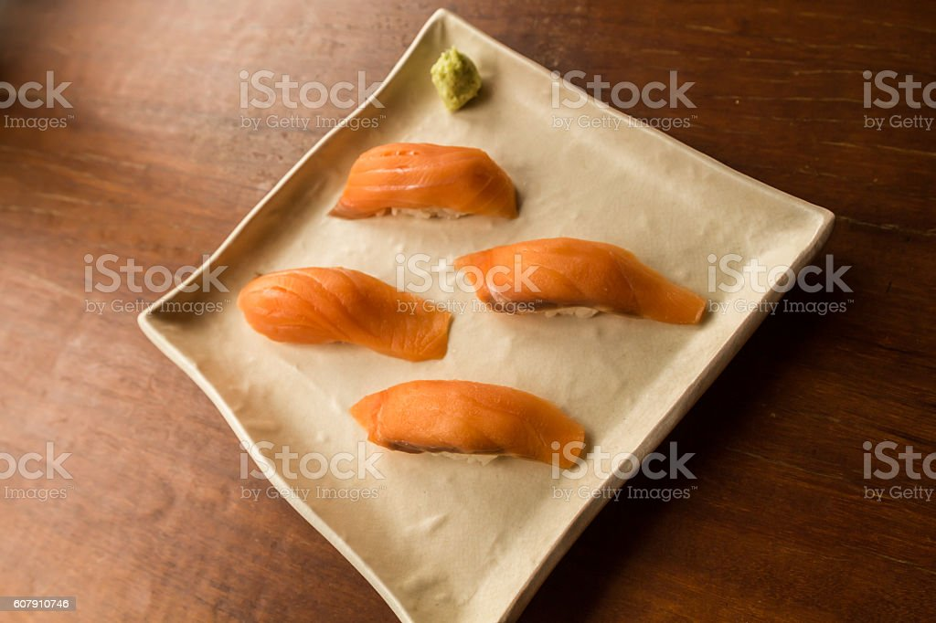 Fresh japanese salmon sushi in plate on wood table stock photo