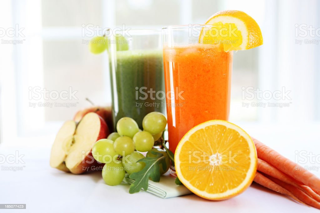 Fresh juice in glasses surrounded by fruits and vegetables stock photo