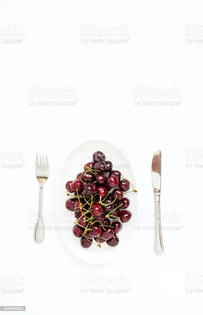 Fresh juicy cherry berries on white plate, served with cutlery, stock photo