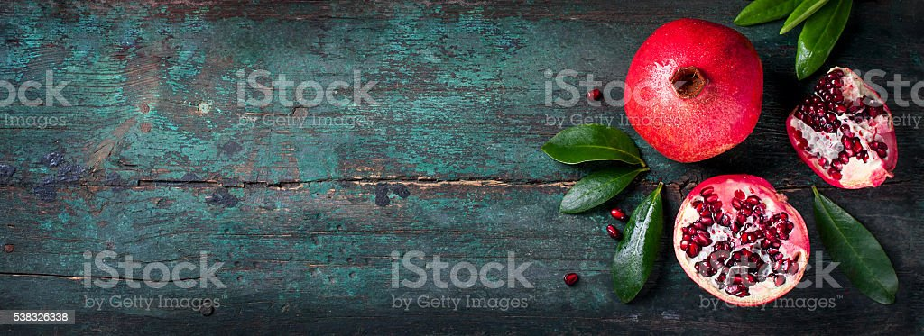 Fresh juicy pomegranate - whole and cut, with leaves stock photo