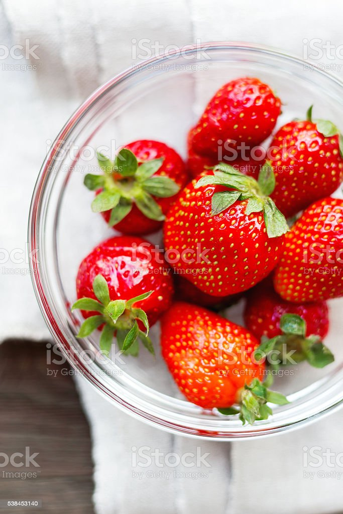 Fresh juicy strawberries in glass bowl. Rustic background stock photo